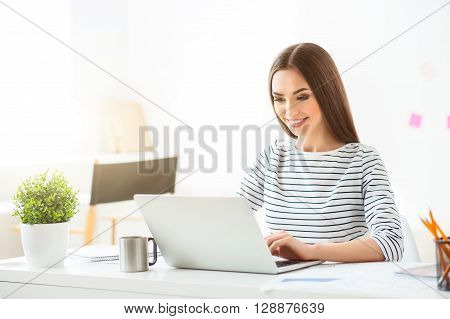Best work for me. Cheerful charming smiling woman sitting at the table and using laptop while being involved in work
