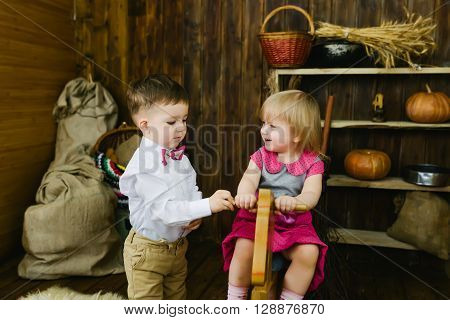 Children ride on the wooden horse in the barn