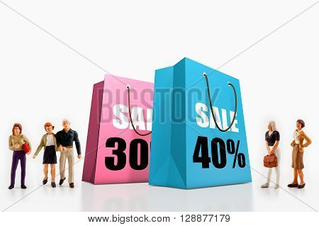 miniature people  - people standing in front of paper bags with printed big sale.