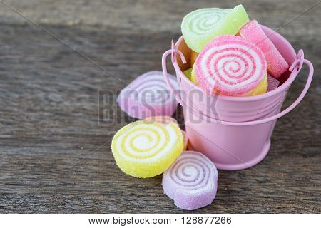 Jelly sweet flavor fruit candy dessert colorful on wooden background and small pink bucket.
