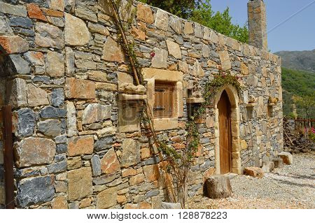 Blue stone Cretan typical house with a vineyard and a window and a wooden door ** Note: Soft Focus at 100%, best at smaller sizes