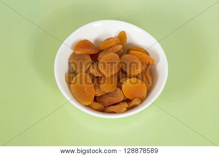 Dried apricots in a white bowl on a green background.