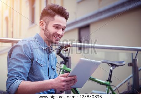 Involved in network. Overjoyed smiling handsome guy using tablet and resting near his bicycle while expressing gladness