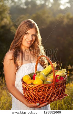 Smiling woman 22-26 year old holding fruit basket outdoors. Looking at camera. Healthy lifestyle. Organic food.