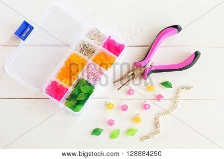 Organizer with beads, plastic flowers and accessories for handmade jewelry on white wooden background. Pliers, metal chain. How to make handmade bracelet. DIY concept