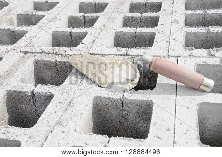 Trowel on cinderblock gray background. against the background of the brickwork is trowel.