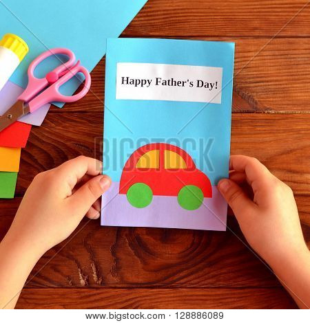 Child holds a card in his hands. Greeting card Happy father's day. Paper sheets, scissors, glue. How to make a greeting card father's day