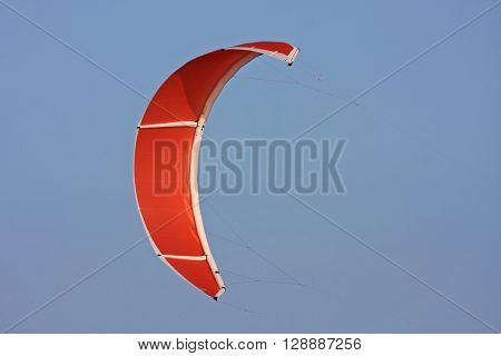 Orange Power kite flying in a blue sky ** Note: Soft Focus at 100%, best at smaller sizes