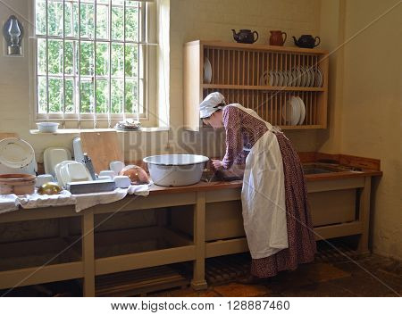 Saffron Walden, Essex, England - May 07, 2016: Young woman dressed as Victorian kitchen maid washing dishes in sink.
