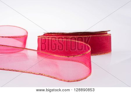 A roll of red ribbon isolated on white