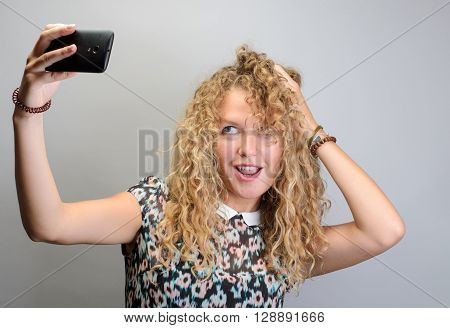 Funky Selfie. Cheerful Young Woman Making Selfie On Her Smart Phone While Standing Against Grey Back