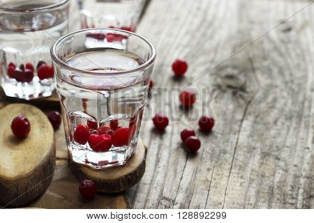 Glasses of vodka with fresh cranberry wooden background rustic style selective focus