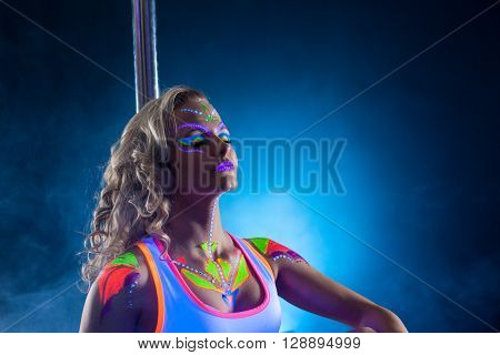 Beautiful pole dancer posing with her eyes closed under UV light