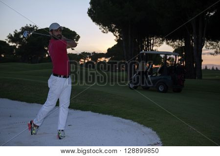 golf player shot ball from sand bunker at course with beautiful sunset with sun flare