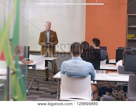 Handsome senior teacher and students group in computer lab classroom. Experienced professor using tablet computer while presenting lessons to class.