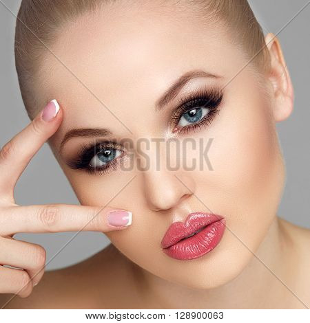 Portrait of glamorous and elegant women, close-up portrait, hold the fingers near the eyes, French manicure, gentle clean skin, big eyes, luxury makeup, beauty salon