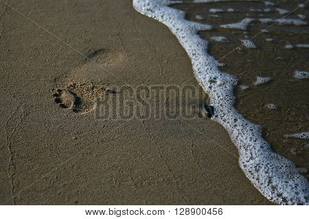 wave and footmark on the seaside at sunset