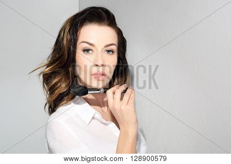 Face modeling, brush for makeup. Beautiful woman holds in her hand a professional makeup brush