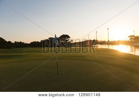golf ball on edge of course hole representing achievement and success business concept, beautiful sunset in background