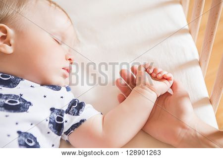 Peaceful adorable baby sleeping on his bed in a room. Soft focus. Sleeping baby concept. year-old babyboy sleeps at home close up. Mum holds by the hand her sleeping child