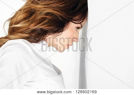 Beautiful young woman based her forehead against the wall.