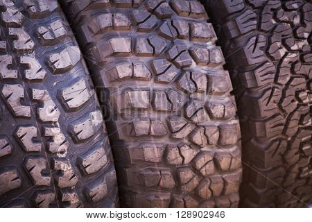 Color close up of some knobby car tires.