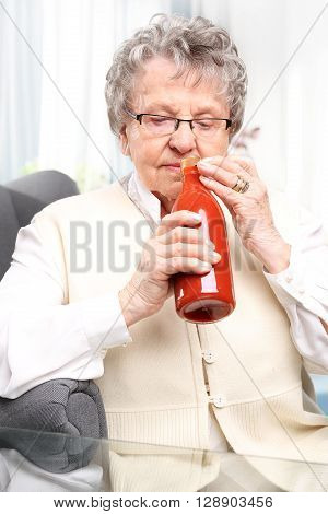 An elderly woman with a bottle personally prepared processed tomato products