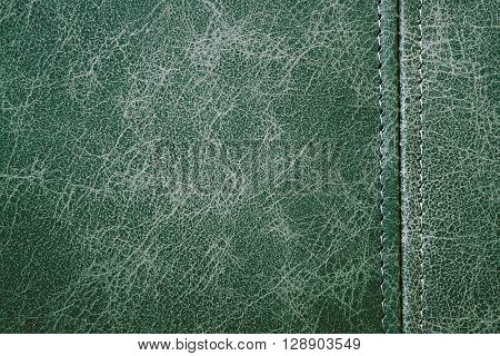 Texture green leather with seam closeup background