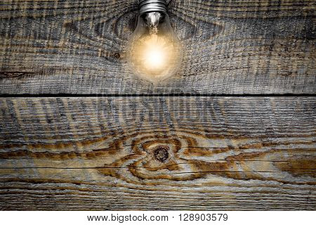 Light bulb glowing on wooden background close up