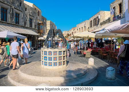 RHODES ISLAND GREECE - JULY 4: Tourists visiting and shopping at square of the Jewish Martyrs in the historic old town of Rhodes Greece on July 4 2015. Rhodes is an island in Greece located in the eastern Aegean Sea