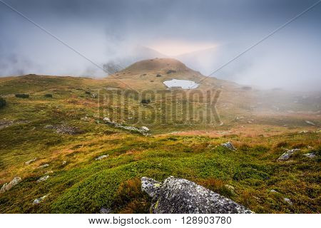 Mountains Landscape in the Mist with a Tarn and Rocks in Foreground