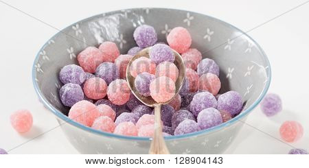Round purple and pink bonbon candies in a bowl on white canvas background closeup. Banner image