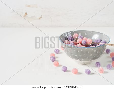 Round purple and pink bonbon candies in a bowl on white rustic background, copy space