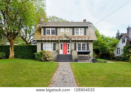 Cozy house with a beautiful garden on a sunny day. Home exterior.