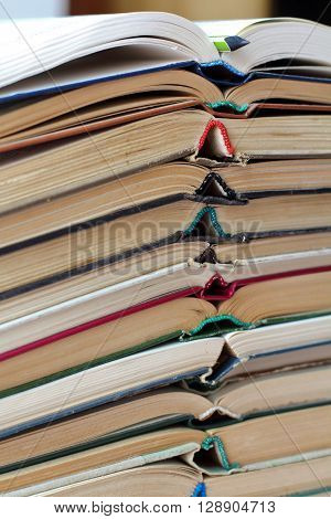stack of opened old books and a pencil vertical