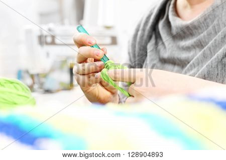 Handicraft knitting crochet. The woman knits crochet.