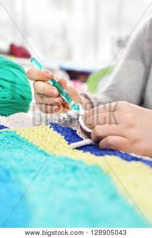 Handicraft. Knitting crochet. The woman knits crochet.