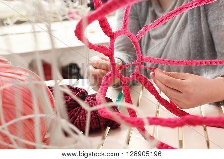 Handicraft, knitting crochet. The woman knits crochet.