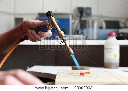 Worker workshop melted metal using a gas burner .