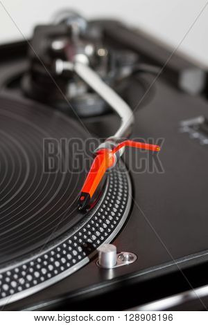 Professional turntable playing vinyl records with music. Close up on details : needle tonearm platter vinyl record