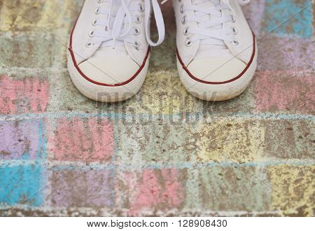 Kid In White Sneakers Stand On Crayon Chalk Drawing