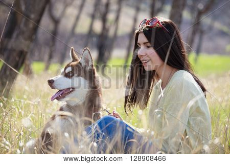 Smiling young brunette girl sitting with her husky dog in green park outdoors. Cute and friendly couple enjoying the nature. Pretty female and fluffy doggy