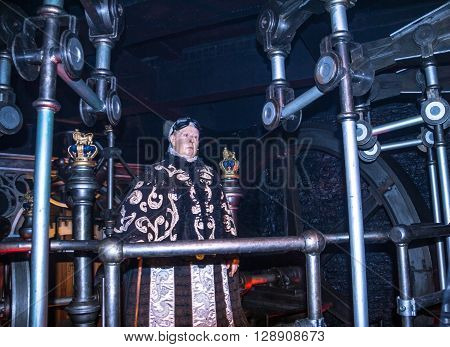 LONDON , UK - JUNE 7, 2015:   Queen Elizabeth I wax figure in old age inspects industrial plant  at Madame Tussauds  MuseumAt one of halls of historical part of Madame Tussauds museum. Madame Tussauds London is famous for recreating famous people and cele