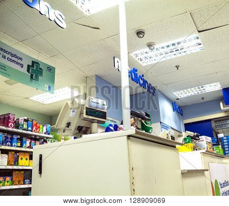 LONDON UK - JUNE 7 2015: Interior of old drug store with bar stools at Baker street. You can see the shelves with merchandise and seller stand with a cash register. Bottom view