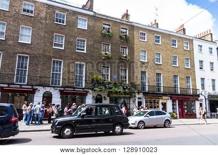 LONDON UK - JUNE 6 2015^ Unidentified tourists near facade of the Sherlock Holmes house and museum in 221b Baker Street. Here is where Arthur Conan Doyle located the studio of the famous detective.