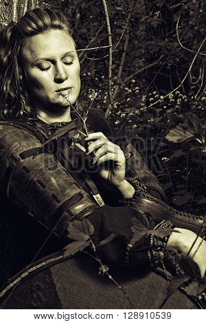 Beautiful scandinavian woman sitting in a forest with shield