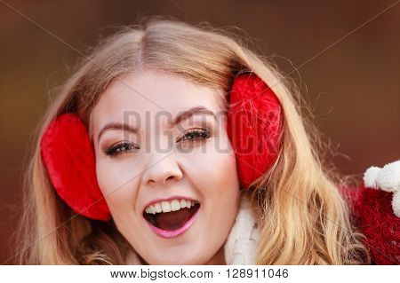Portrait of pretty smiling fashionable woman in fall forest park. Happy gorgeous young girl in red earmuffs. Autumn winter fashion.