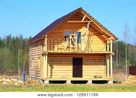 Construction of lumber cottage on the edge of forest