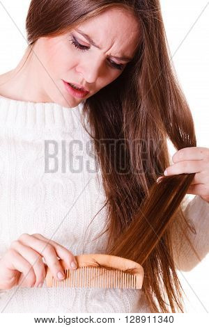 Dissatisfied woman combing with brush and pulls at her long hair. Feeling pain for nice look in daily activity.