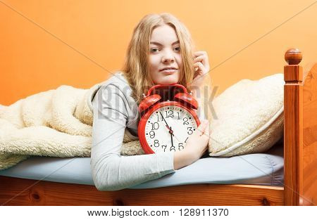 Woman Waking Up With Alarm Clock In Morning